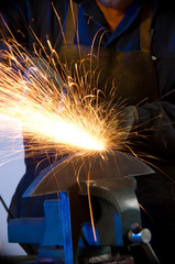 Factory worker makes sparks using electric grinder isolated.