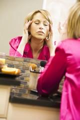 Woman Massaging Her Head In Mirror