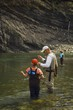 Father And Sons Fly Fishing In Mountain River