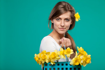 Portrait of young female holding bunch of flowers in paper-bag