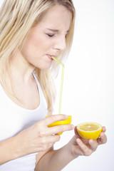 Frau trinkt mit Strohhalm direkt aus Zitrone, Augen zu
