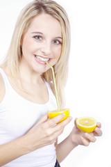 Frau trinkt mit Strohhalm direkt aus Zitrone, sauer macht lustig