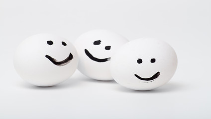 three white smiling eggs