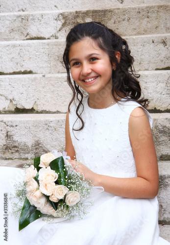 Bambina sorridente con vestito bianco