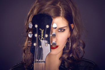 Frau mit Gitarre vor Gesicht