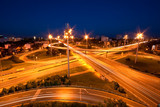 Cars moving through highway intersection at dusk poster