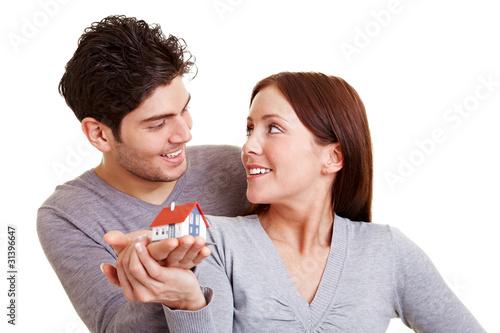 Lachendes Paar hält Haus