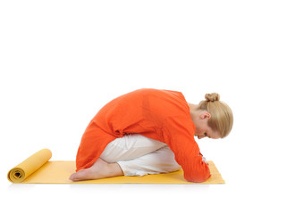 series or yoga photos.young woman in virasana pose on yellow pil