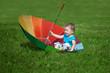 Little boy with a big rainbow umbrella