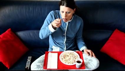 Bella ragazza che mangia sul divano davanti alla tele II