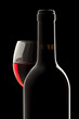 Elegant red wine bottle and wine glass in a black background