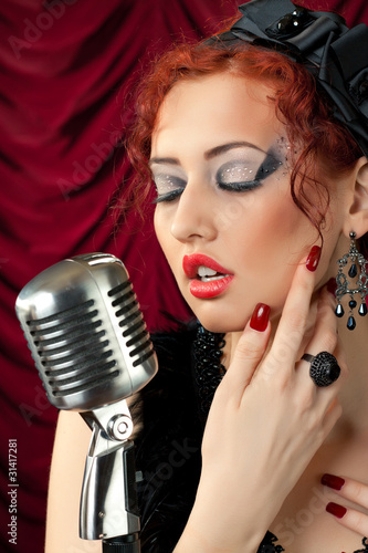 beautiful redhead woman singing into vintage microphone