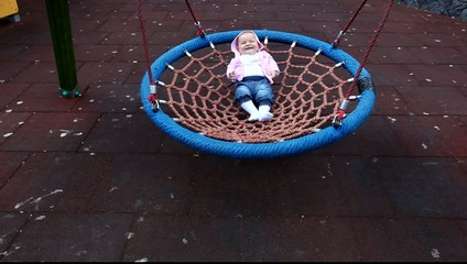 Happy baby girl in a swing