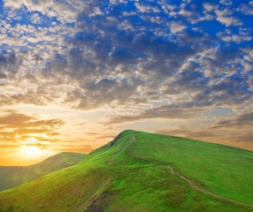 dramatic sunset in a green hills