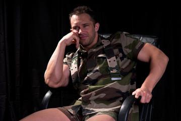homme en tenue kaki assis dans un fauteuil 5