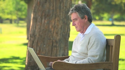 Elderly man using his laptop on a bench