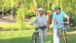 Mature couple walking with their bikes