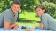 Young couple playing chess while lying on the grass