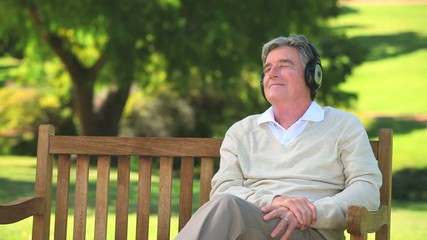Mature man listening to music with his headphones