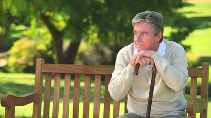 Mature man thinking on a bench