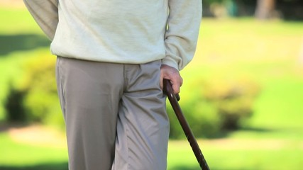 Mature man thinking while holding his walking stick