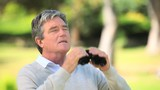 Mature man watching something through binoculars