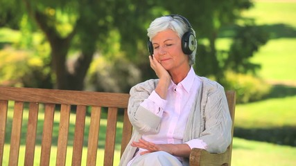 Mature woman listening to music outside