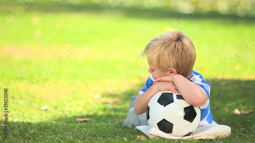 Young boy lying on the grass with his ball