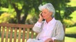 Mature woman phoning on a public bench