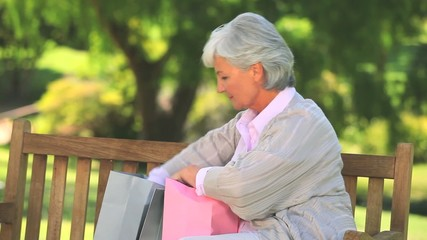 Mature woman on a park bench with her shopping