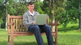 Young man chatting on his laptop on a bench