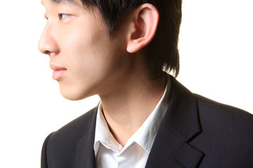 Young businessman standing and looking right,