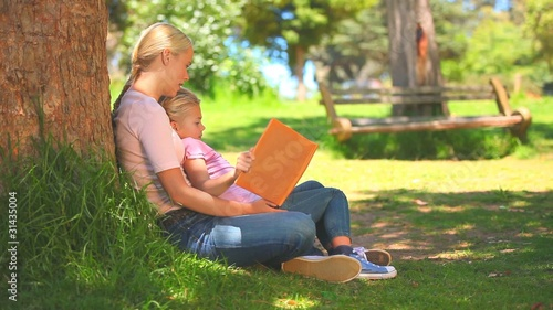 Young woman reading a book with her daughter