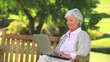 Mature woman surfing on her laptop outdoors