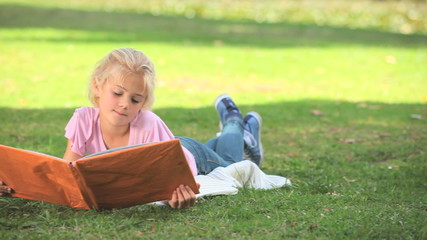 Young girl reading a book on the grass