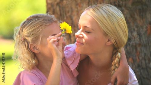 Young girl and her mother playing with a flower