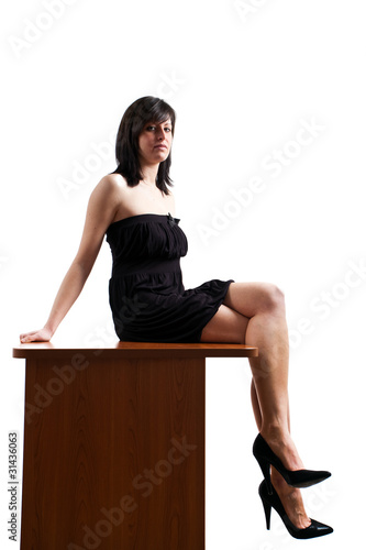 flirting sexy business woman is sitting on table in the office
