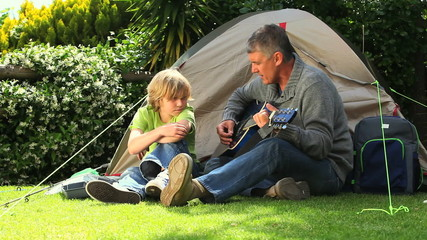 Man playing guitar with son outside tent in garden