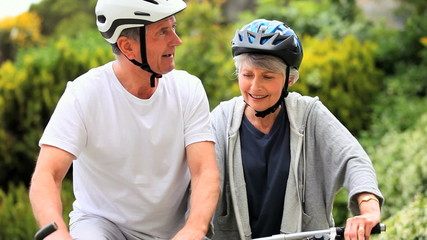 Mature couple on bycycles having a break