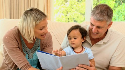Parents looking at book with baby