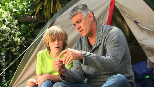 Father showing son how to prepare fishing tackle