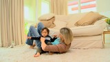 Mother playing with baby lying on a carpet