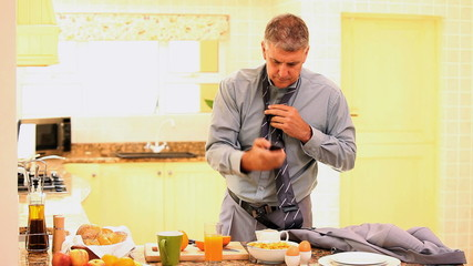 Man trying to get dressed while eating and receiving a call