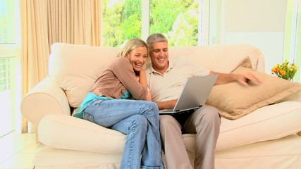 Couple enjoying pictures on laptop on sofa