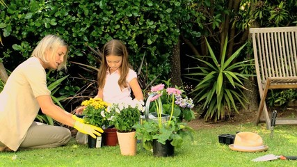 Mother and daughter potting flowers on lawn