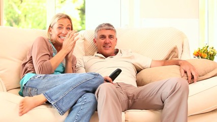 Couple watching hilarious programme on TV