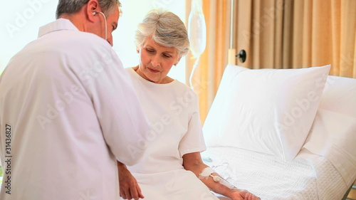 Doctor attending to woman in hospital bed