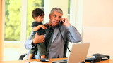 Man doing office work while holding baby