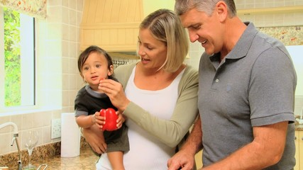 Couple in the kitchen holding baby and preparing food