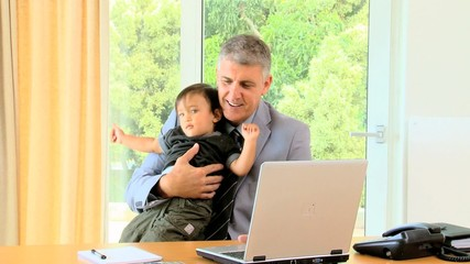 Man working on laptop and phoning while holding baby
